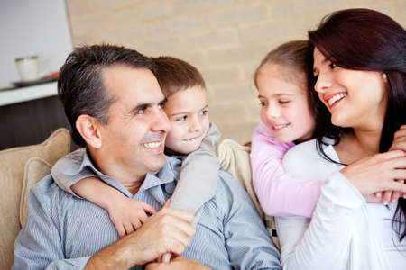 Family portrait indoors with parents and kids smiling  photo