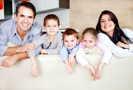 Happy family portrait leaning on the sofa and smiling Stock Photo - 12824421