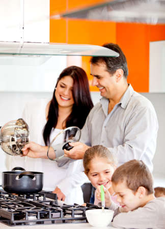 Happy family in the kitchen cooking dinner together    photo