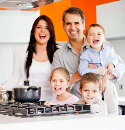 Happy family cooking dinner at home and smiling  photo