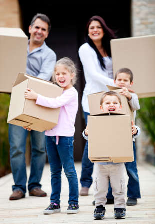 Family moving home and carrying cardboard boxes outdoors photo