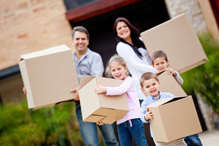 family moving house: Happy family moving house and carrying boxes Stock Photo