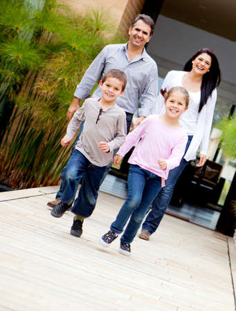 Happy family with kids running outside their house  photo
