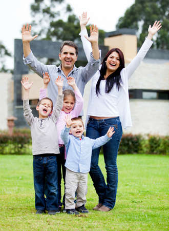 Happy family with arms up standing in their backyard  photo