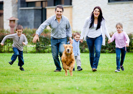 Happy family running with their dog outdoors  photo