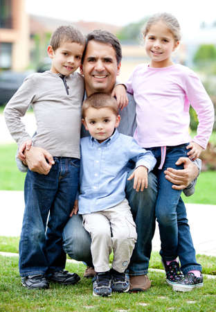 Lovely family portrait of father with his children smiling outdoors  photo