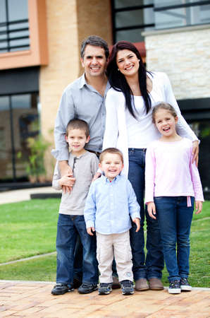 Family standing in front of their house and smiling  Stock Photo - 13153464