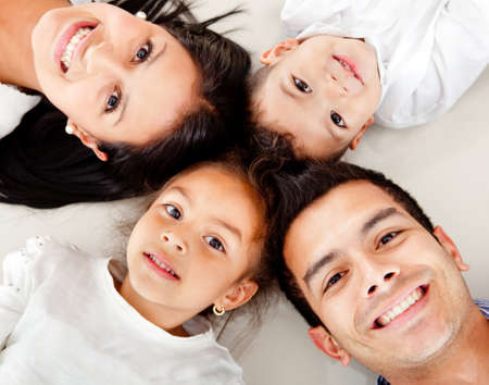 latinos: Beautiful family portrait lying on the floor with heads together
