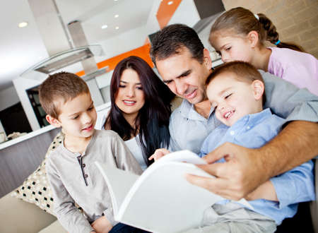 Beautiful family reading a book together at home  Stock Photo - 13153607