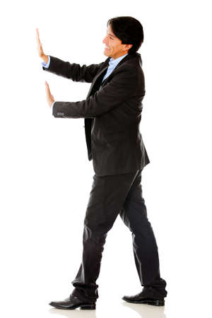 Business man pushing something with his hands - isolated over a white background photo
