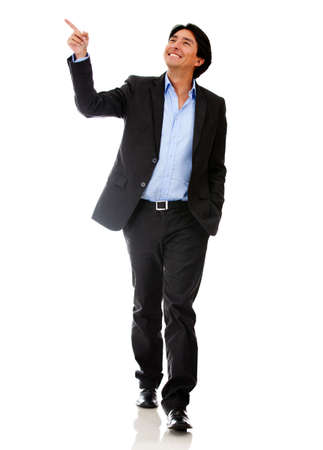 Happy businessman walking and pointing - isolated over a white background  photo