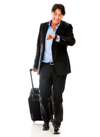 Business man checking the time for his trip - isolated over a white background  photo