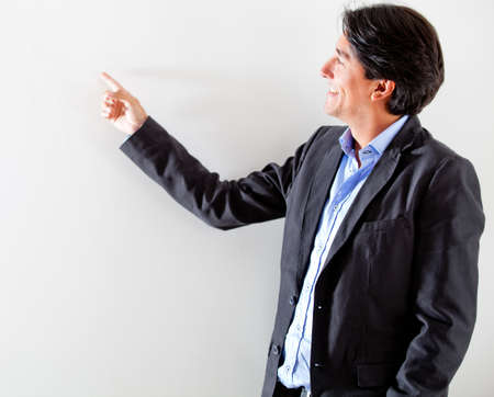 Businessman pointing at the wall - isolated over a white background  photo