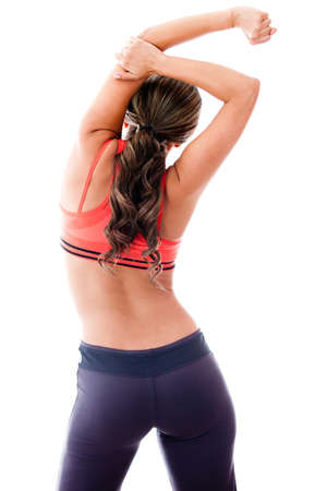 Fit woman stretching her back - isolated over a white background photo