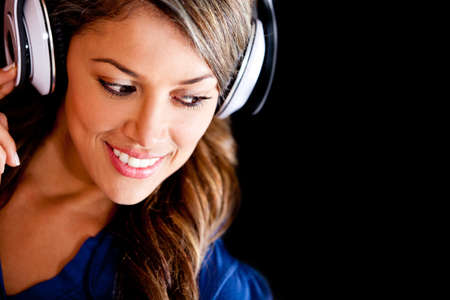 Beautiful woman portrait with headphones - isolated over black  photo
