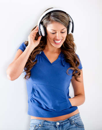 listen to music: Casual woman listening to music with headphones  Stock Photo