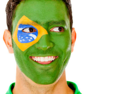 painted face: Happy Brazilian man with flag painted on his face - isolated