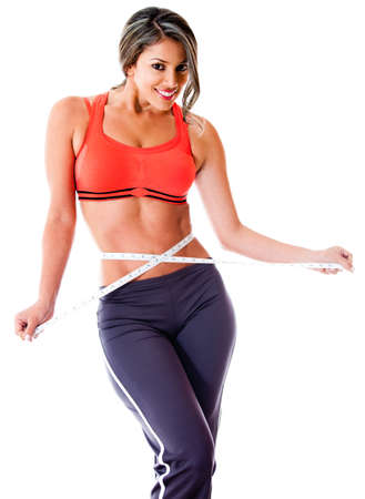 Fit woman measuring her waist - isolated over a white background  photo