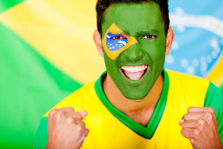 Happy Brazilian man with the flag painted on his face  photo