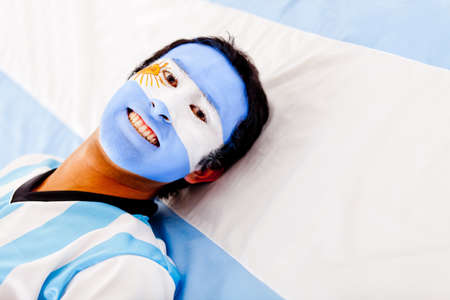 Man with the Argentinean flag painted on his face  Stock Photo - 13227030