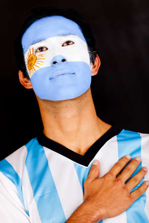 Proud Argentinean man with hand on heart - isolated over a black background  photo
