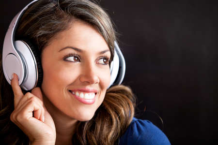 Woman portrait listening to music with headphones and smiling  photo