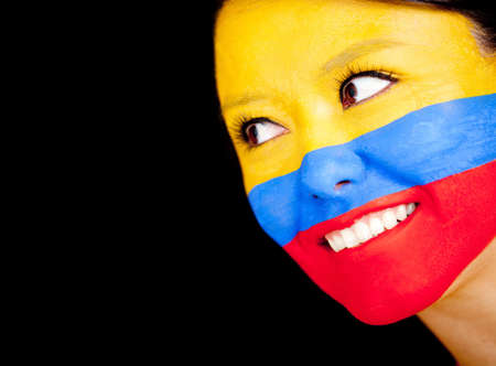 Woman with the flag Colombia painted on her face - isolated over a black background  photo