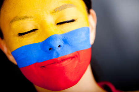 Portrait of a Colombian woman with the flag painted on her face  photo