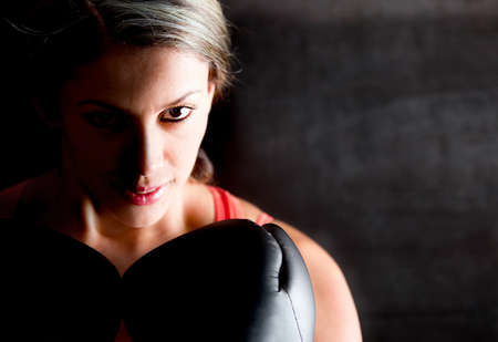 aggressive people: Portrait of a female boxer looking aggressive with her gloves  Stock Photo