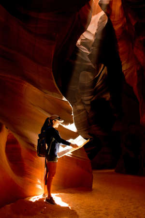 find us: Female explorer inside a cave at the Grand Canyon  Stock Photo