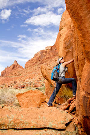 Female explorer at the desert climbing a rocky mountain  photo