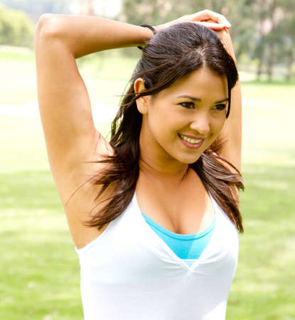 Woman doing stretching exercises for her arms outdoors  photo