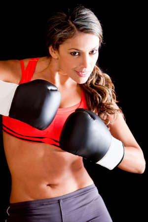 boxing training: Female boxer wearing boxing gloves - isolated over a black background