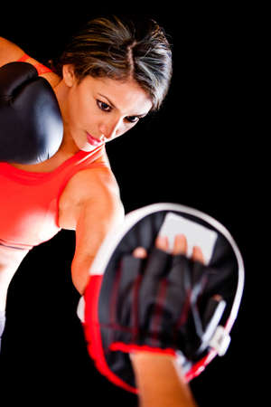 Atheltic woman working out boxing - isolated over a black background  photo