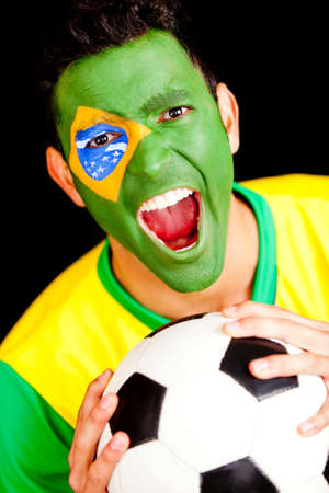 nationalistic: Excited Brazilian football fan scraming with flag painted on his face