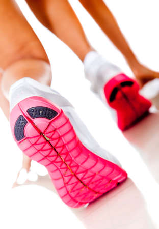 Female athlete racing focus on shoes - isolated over white  photo