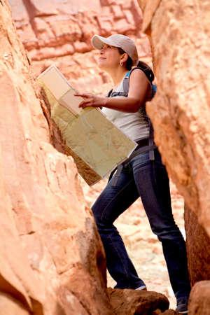 adventurous: Adventurous woman exploring the desert holding a map