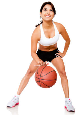 Female basketball player bouncing the ball - isolated over white  photo