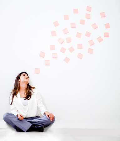 Thoughtful business woman with a bubble of post its - isolated over white  photo
