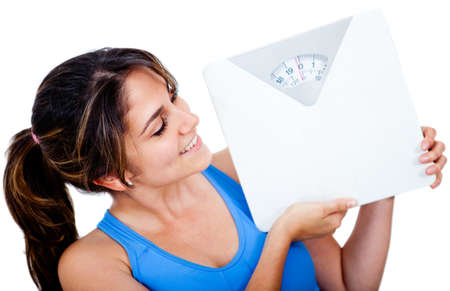 Woman loosing weight holding a scale - isolated over a white background  photo