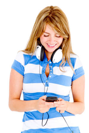 Young woman with headphones listening to music on cell phone - isolated  Stock Photo - 13440610