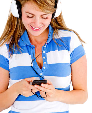 Woman listening to music on her cell phone - isolated over white  photo