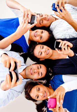 mobiele telefoons: Groep jonge mensen sms op hun mobiele telefoons en glimlachen
