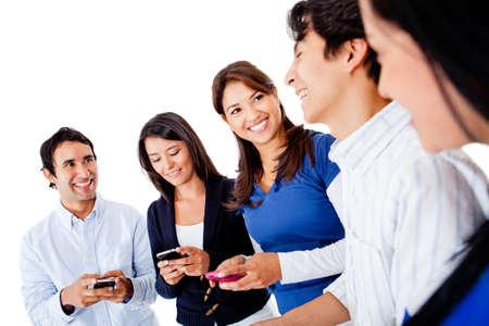 mobiele telefoons: Groep van vrienden sms op hun mobiele telefoons - die over een witte achtergrond Stockfoto