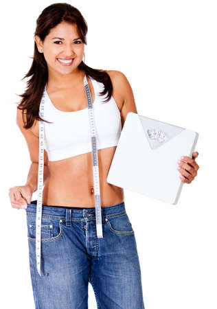 Woman loosing weight in baggy clothes and holding a scale - isolated over white  photo
