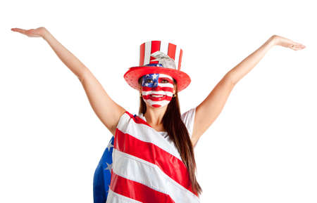 Happy American woman with the USA flag painted on her face and a hat   photo
