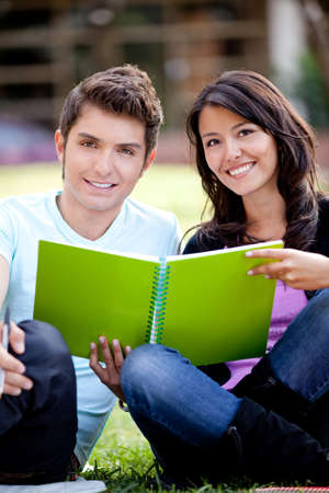 Couple of students sitting outdoors studying and smiling  photo