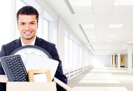 moving office: Businessman moving into a new office holding a box  Stock Photo