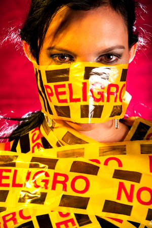 Woman with a caution tape warning of danger Stock Photo - 13620318