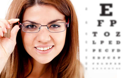optometry: Woman taking an eye vision test and wearing glasses